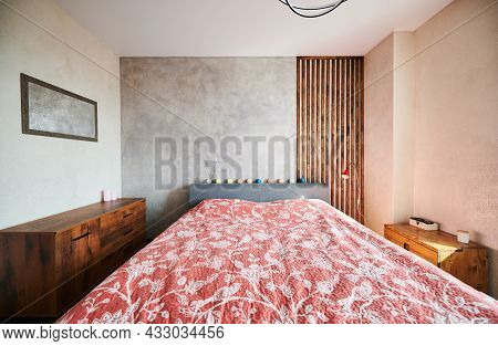 View Of Design Of Slipping Room With Big Bed With Red Floral Blanket. Bedroom With Two Wooden Commod