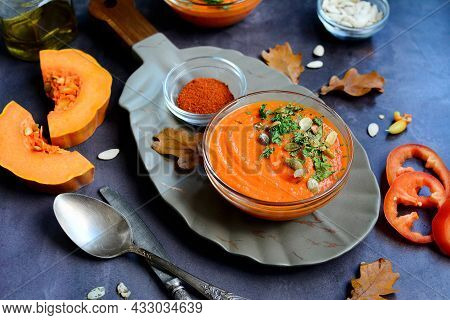 Close-up Of Orange Pumpkin Puree Soup In A Bowl, Pepper, Paprika, Spices, Herbs, Pumpkin Slices On A