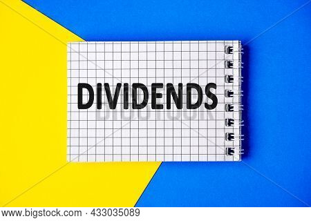 Text Dividends On Page Notebook With Cage Lies On A Blue And Yellow Background, Top View.