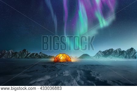 A Tent Pitched Up In Snow At Night With The Northern Lights Flickering In The Sky Above. Aurora Bore