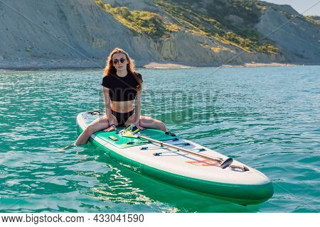 May 28, 2021. Anapa, Russia. Young Girl Posing On Stand Up Paddle Board At Black Sea. Woman Vacation