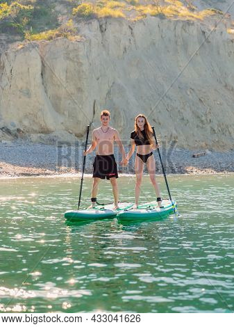 May 28, 2021. Anapa, Russia. Young Couple On Stand Up Paddle Board At Quiet Sea. Vacation On Red Pad
