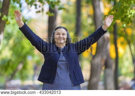 Happy Woman With Arms Outstretched In Autumn Park. Happiness And Positivity Concept