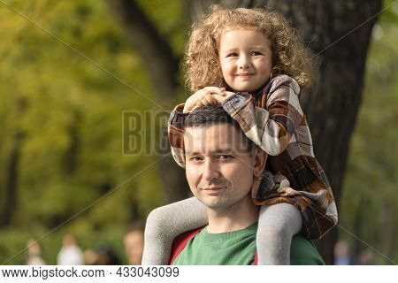 Happy Family. Laughing Daughter Sitting On Dad's Shoulders. Father's Day. Cute Little Girl Walking W