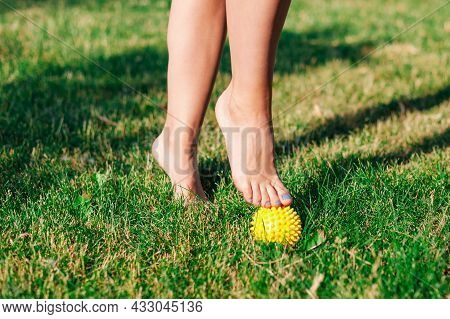 Close-up Of Graceful Bare Feet Of Young Woman Standing On Tiptoes On Spiked Massage Ball On Green La