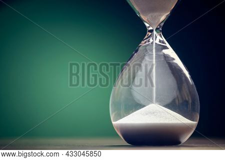 Hourglass time passing green background concept for business deadline, urgency and running out of time