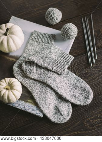 Hand Knitting Socks With Needles And Yarn Balls On A Dark Wooden Background.  Concept For Handmade A