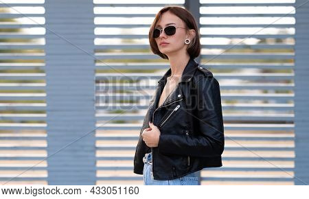 Portrait Of A Girl With Short Hair In A Leather Jacket In The Autumn Forest. Young Hipster Or Rocker