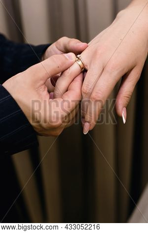 The Groom Puts Wedding Ring On The Bride's Finger. The Man, The Groom, At The Wedding Ceremony Gentl