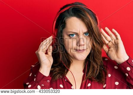 Young caucasian woman listening to music using headphones skeptic and nervous, frowning upset because of problem. negative person.