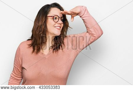 Young plus size woman wearing casual clothes and glasses very happy and smiling looking far away with hand over head. searching concept.