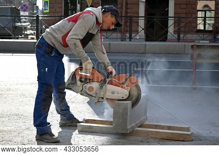 Saint Petersburg, Russia-september 2021. A Male Bricklayer Cuts A Granite Stone With A Special Tool