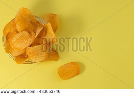 Bowl With Potato Chips On A Yellow Background. Top View, Copy Space.