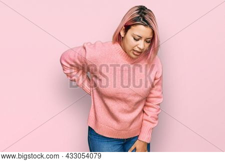 Hispanic woman with pink hair wearing casual winter sweater suffering of backache, touching back with hand, muscular pain