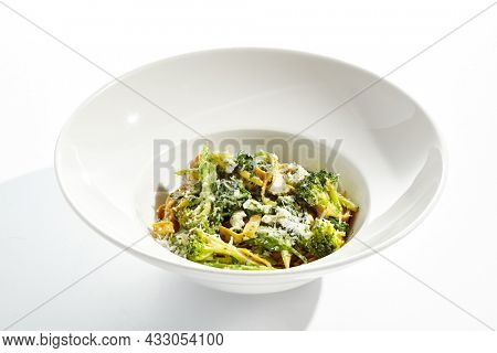 Veggie pasta with broccoli isolated on white background. Vegetarian dish - udon noodle with green vegetables. Vegan food in restaurant menu. Plant based dinning