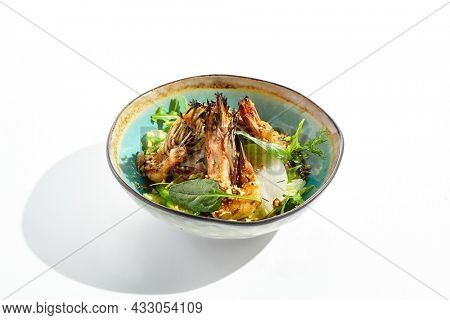 Green salad with grilled prawns and vegetables. Healthy food in restaurant menu. Shrimp with salad mix and peanuts - delicious dish for keto diet. Restaurant dish isolated on white background