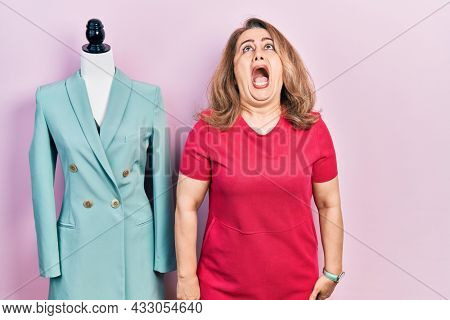 Middle age caucasian woman standing by manikin angry and mad screaming frustrated and furious, shouting with anger. rage and aggressive concept.