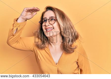Middle age caucasian woman wearing casual clothes and glasses very happy and smiling looking far away with hand over head. searching concept.