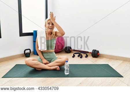 Young caucasian woman sitting on training mat at the gym surprised with hand on head for mistake, remember error. forgot, bad memory concept.