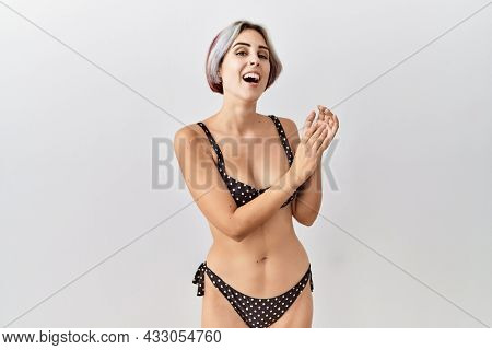 Young beautiful woman wearing swimsuit over isolated background clapping and applauding happy and joyful, smiling proud hands together