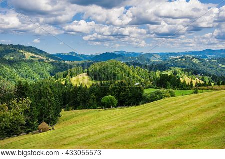 Pastures Of Young Green Grass On The Slopes Of The Mountains Against The Backdrop Of A Beautiful Blu