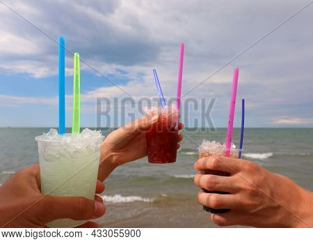 Three Hands Of The Boys And Girl Who Make A Toast With Frozen Grenadines To Celebrate By The Sea