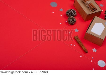 Composition of christmas decorations with pine cones, cinnamon and copy space on red background. christmas, tradition and celebration concept.