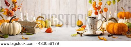 Autumn still life with cup of tea, pumpkins, flowers and candles on table.Thanksgiving day or halloween concept. Banner