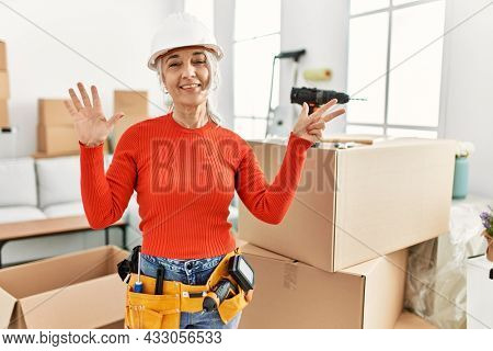 Middle age grey-haired woman wearing hardhat standing at new home showing and pointing up with fingers number eight while smiling confident and happy.