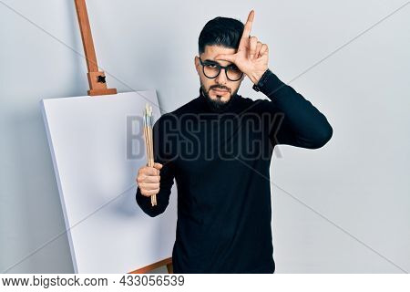 Handsome man with beard holding brushes close to easel stand making fun of people with fingers on forehead doing loser gesture mocking and insulting.