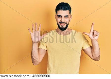 Handsome man with beard wearing casual yellow t shirt showing and pointing up with fingers number seven while smiling confident and happy.