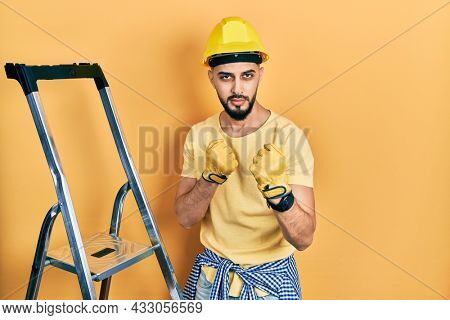 Handsome man with beard by construction stairs wearing hardhat ready to fight with fist defense gesture, angry and upset face, afraid of problem