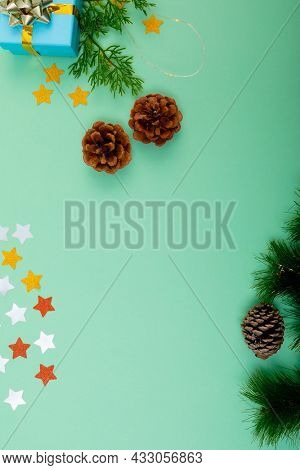 Composition of christmas decorations with pine cones and copy space on green background. christmas, tradition and celebration concept.