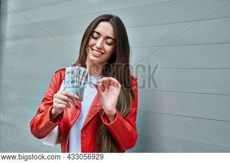 Young hispanic woman smiling happy counting peruvian sol banknotes at the city.
