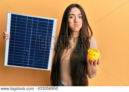 Young hispanic girl holding photovoltaic solar panel and piggy bank puffing cheeks with funny face. mouth inflated with air, catching air.