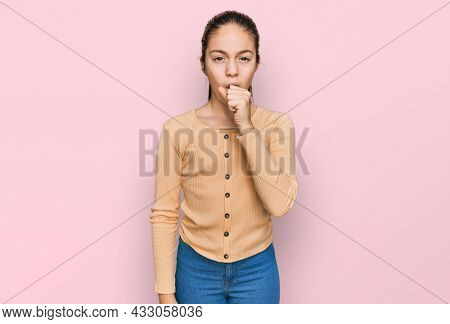 Beautiful brunette little girl wearing casual sweater feeling unwell and coughing as symptom for cold or bronchitis. health care concept.