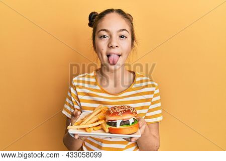Beautiful brunette little girl eating a tasty classic burger with fries sticking tongue out happy with funny expression.