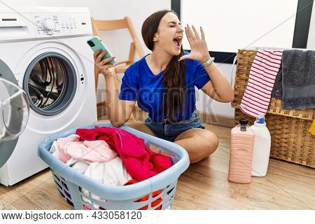 Young brunette woman doing laundry using smartphone shouting and screaming loud to side with hand on mouth. communication concept.