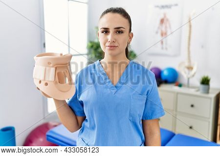 Young physiotherapist woman holding cervical neck collar at medical clinic thinking attitude and sober expression looking self confident