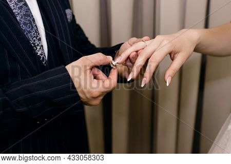The Groom Puts A Gold Wedding Ring On The Bride's Finger Close-up. The Man The Groom Gently Holds Th