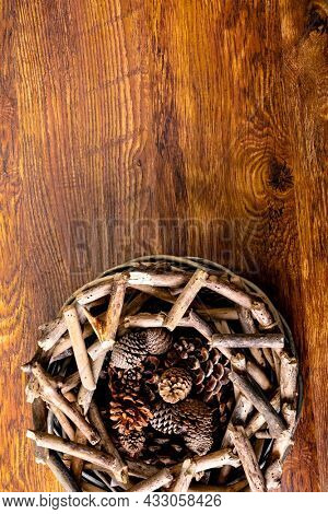 Composition of christmas decorations with sticks, pine cones and copy space on wooden background. christmas, nature, tradition and celebration concept.
