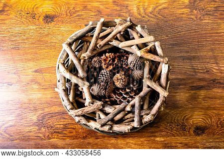 Composition of christmas decorations with sticks and pine cones on wooden background. christmas, nature, tradition and celebration concept.