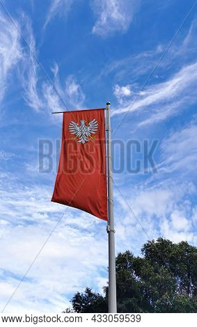 The State Flag Of Poland With The Emblem Of The Republic Of Poland, Waving In The Wind On The Left O