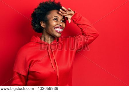 Young african american woman wearing casual sweatshirt very happy and smiling looking far away with hand over head. searching concept.