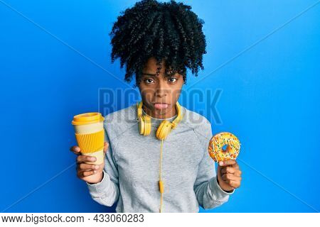 African american woman with afro hair eating doughnut and drinking coffee depressed and worry for distress, crying angry and afraid. sad expression.