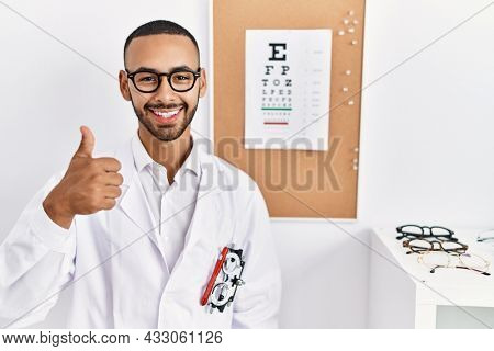 African american optician man standing by eyesight test doing happy thumbs up gesture with hand. approving expression looking at the camera showing success.