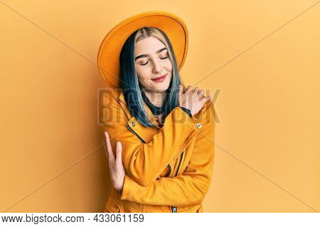 Young modern girl wearing yellow hat and leather jacket hugging oneself happy and positive, smiling confident. self love and self care