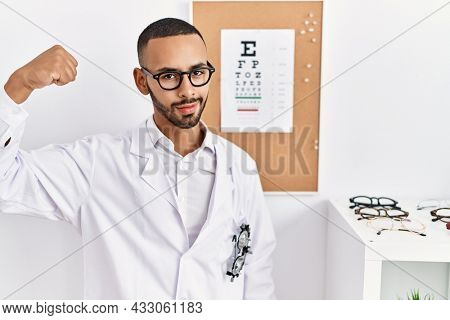 African american optician man standing by eyesight test strong person showing arm muscle, confident and proud of power