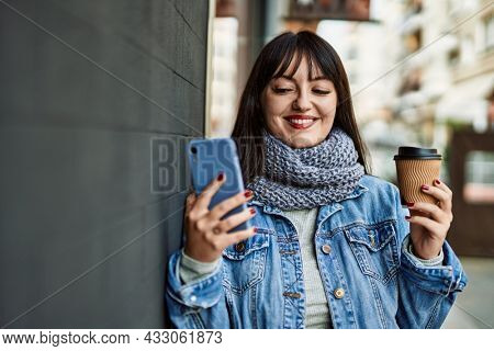 Young brunette woman smiling happy using smartphone and drinking a cup of coffee leaning on the wall