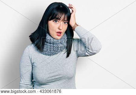 Young hispanic plus size woman wearing winter scarf surprised with hand on head for mistake, remember error. forgot, bad memory concept.